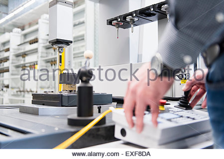 Factory worker hands operating control panel in factory - Stock Photo