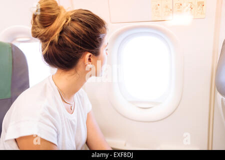 Young woman looking out of airplane window - Stock Photo