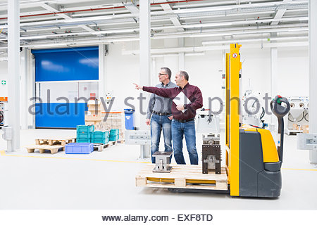 Manager and factory worker meeting in warehouse - Stock Photo