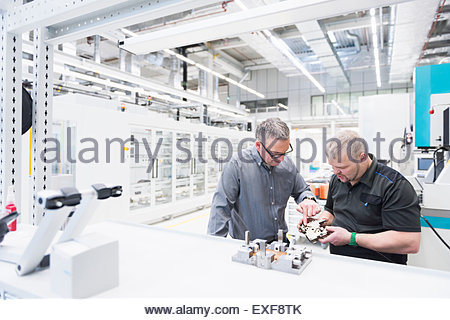 Two factory workers checking factory component - Stock Photo