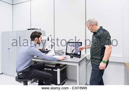 Factory engineers looking at microscopic image in factory - Stock Photo