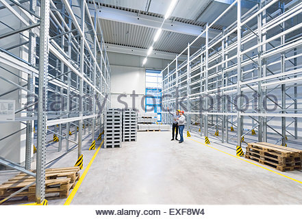 Businessmen meeting in empty factory warehouse - Stock Photo