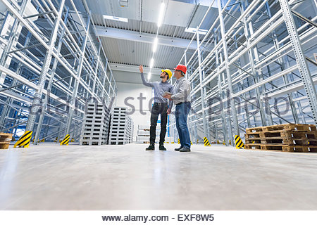 Two businessmen meeting in empty factory warehouse - Stock Photo