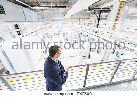 High angle view of manager looking down on factory - Stock Photo