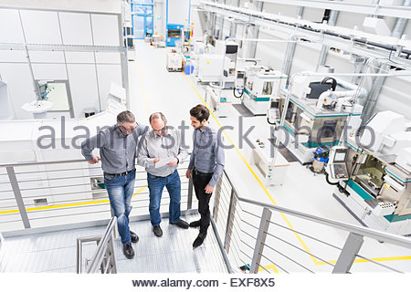 Engineers discussing notes on factory stairway - Stock Photo