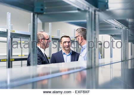 Businessmen and manager chatting in empty factory warehouse - Stock Photo