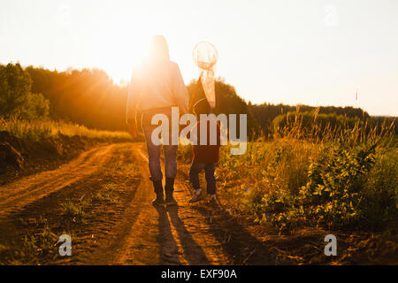 Rear view of father and son with butterfly net walking along dirt track at sunset, Sarsy village, Sverdlovsk Region, - Stock Photo