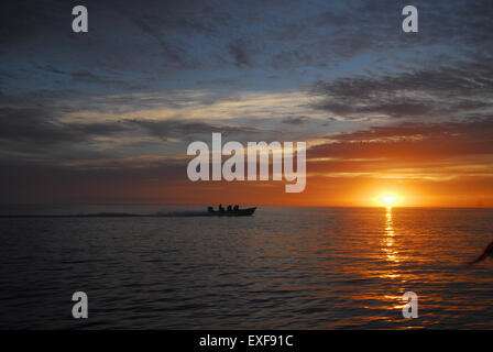 Silhouetted boat at sunrise, Magdalena Bay, Baja, California, Mexico - Stock Photo