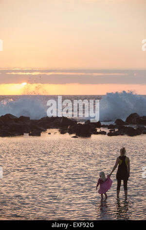 Silhouetted female toddler and mother paddling in sea looking out at waves splashing, Kona, Hawaii, USA - Stock Photo