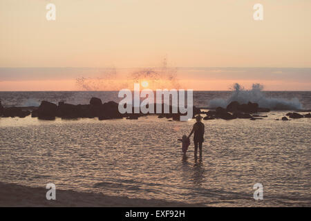 Silhouetted mother and female toddler paddling in sea looking out at waves splashing, Kona, Hawaii, USA - Stock Photo