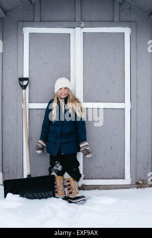 Girl grinning with excitement at snow - Stock Photo