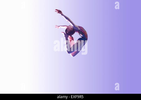 Young gymnast in mid-air leap - Stock Photo