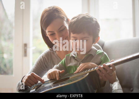 Boy sitting on mother's lap and learning to play guitar - Stock Photo