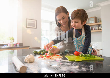 Mother and son preparing pizza together in kitchen - Stock Photo