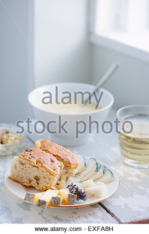 Bowl of soup with focaccia and cheese in kitchen - Stock Photo