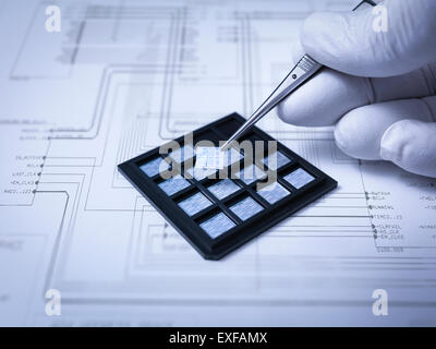 Small electronic chips held in tweezers in laboratory, close up - Stock Photo