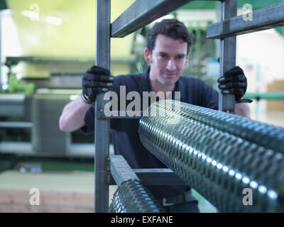 Worker operating carbon fibre loom in carbon fibre factory - Stock Photo