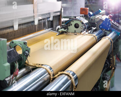 Loom weaving kevlar fabric in carbon fibre factory - Stock Photo