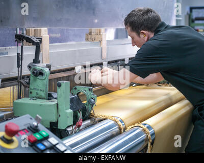 Worker weaving kevlar fabric in carbon fibre factory - Stock Photo