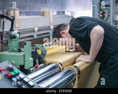 Worker inspecting kevlar fabric in carbon fibre factory - Stock Photo