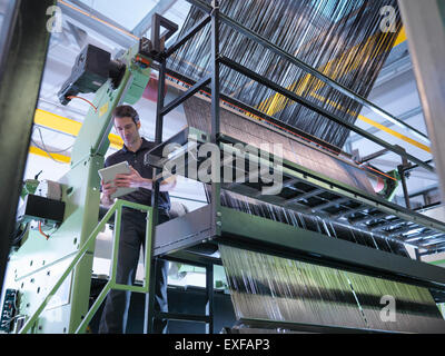 Worker inspecting carbon fibre on loom in carbon fibre factory - Stock Photo