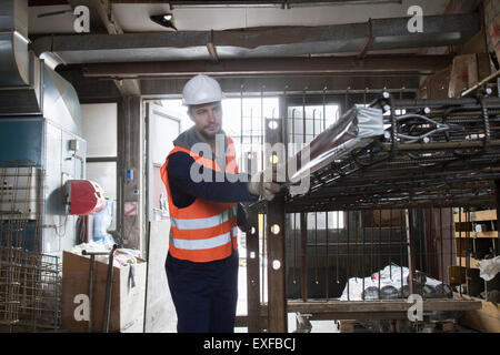 Factory worker selecting steel mesh in concrete reinforcement factory - Stock Photo