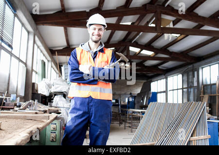 Portrait of factory worker with hammer in concrete reinforcement factory - Stock Photo