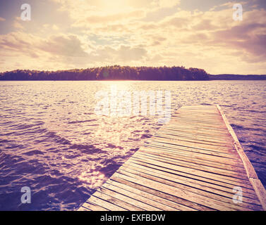 Vintage instagram filtered wooden pier at sunset. - Stock Photo