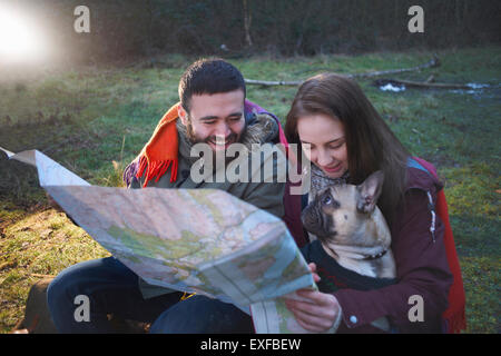 Young hiking couple reading map in woods - Stock Photo