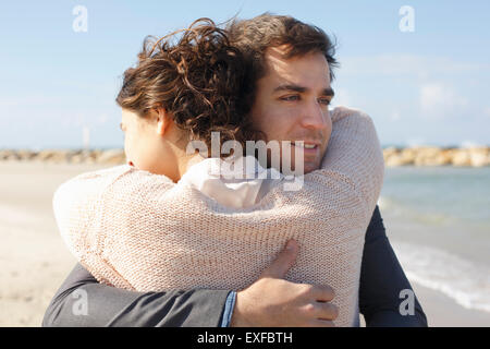 Young couple hugging each other on beach, Tel Aviv, Israel - Stock Photo