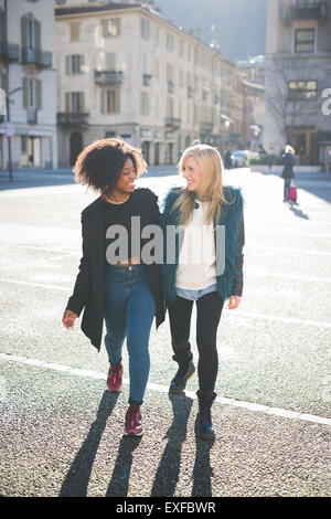Two female friends chatting and strolling in town square - Stock Photo