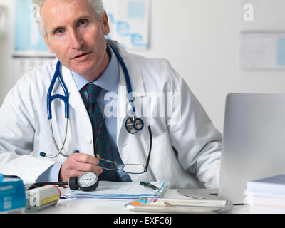 Portrait of doctor consulting a patient in office - Stock Photo