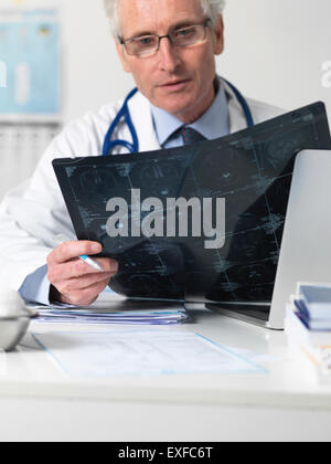 Doctor studying film sheet of computed tomography (CT) scans of various sections through the human head - Stock Photo