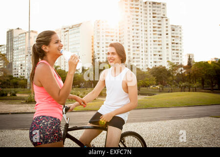 Young couple chatting whilst preparing to cycle in park - Stock Photo