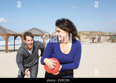 Young couple running with ball on beach, Tel Aviv, Israel - Stock Photo