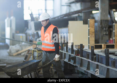 Factory worker pushing wheelbarrow in concrete reinforcement factory - Stock Photo