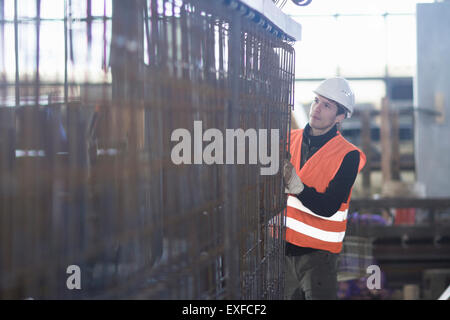 Young male factory worker choosing wire mesh in concrete reinforcement factory - Stock Photo