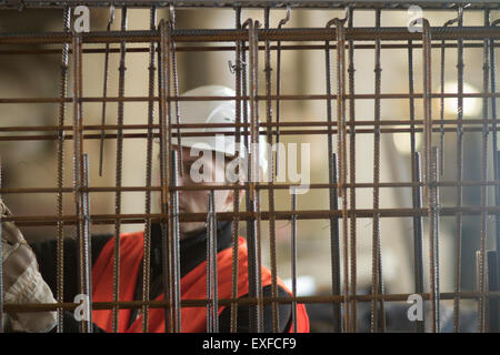 Factory worker selecting wire mesh in concrete reinforcement factory - Stock Photo