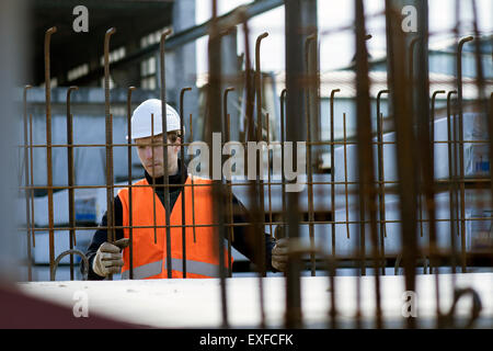Factory worker choosing wire mesh in concrete reinforcement factory - Stock Photo