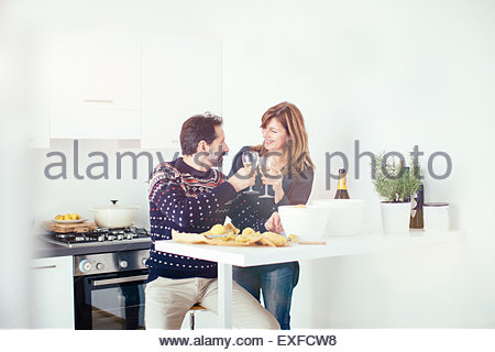 Mature couple toasting and preparing food in kitchen - Stock Photo
