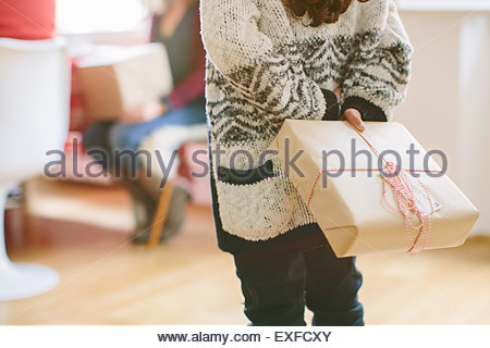 Child hiding surprise gift at family Christmas party - Stock Photo