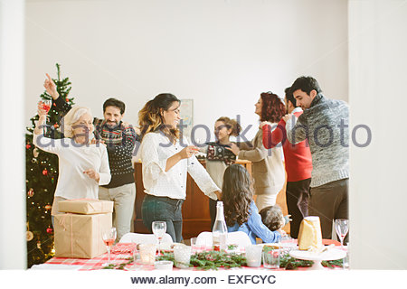Family doing the conga at family Christmas party - Stock Photo