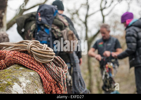 Climbing ropes on rocks with climbers in background - Stock Photo