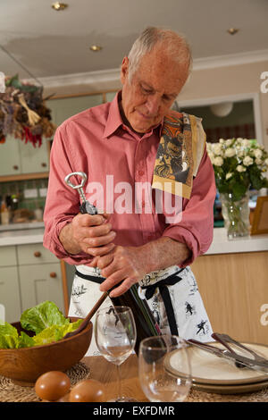 Senior man opening bottle of wine - Stock Photo
