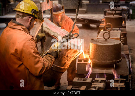 Workers pouring molten metal from flask in foundry - Stock Photo