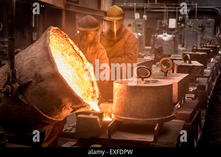 Two workers pouring molten metal from flask in foundry - Stock Photo