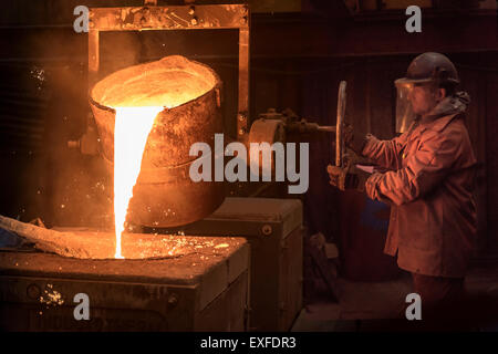 Worker pouring molten metal from flask in foundry