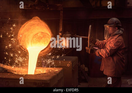 Worker pouring molten metal from flask in foundry workshop
