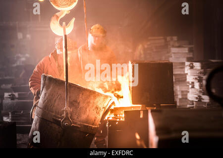 Workers pouring molten metal into moulds from flask in foundry - Stock Photo