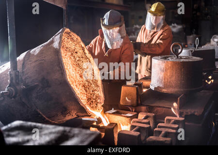 Workers pouring molten metal from flasks into moulds in foundry - Stock Photo